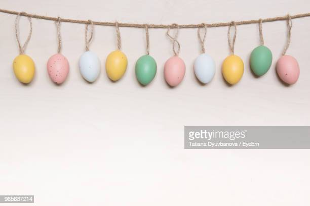 close-up of colorful easter eggs hanging on table - osterei stock-fotos und bilder
