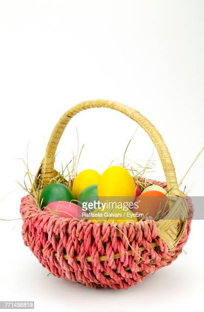 close-up of colorful easter eggs in basket against white background - easter egg foto e immagini stock
