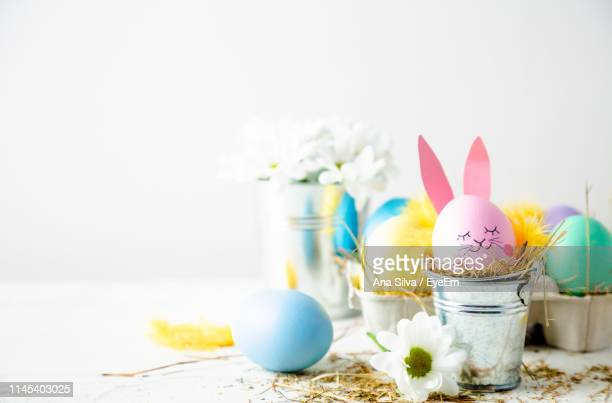 close-up of colorful easter eggs on table against white background - easter bunny stock pictures, royalty-free photos & images