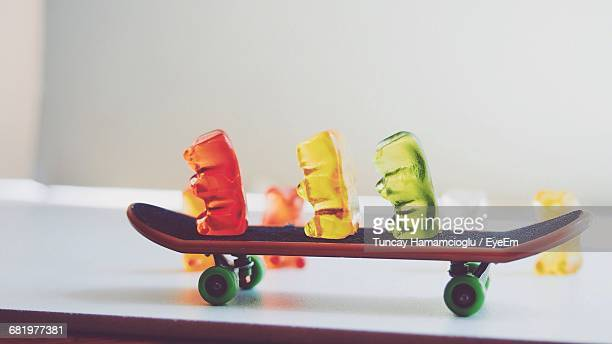close-up of colorful gummi bears on skateboard at table - gummi bears stock photos and pictures