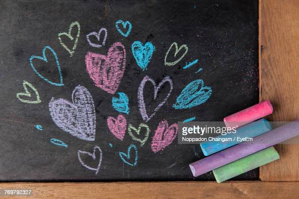 Close-Up Of Colorful Heart Shape Chalk Drawings On Blackboard