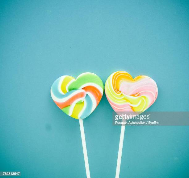 Close-Up Of Colorful Heart Shape Lollipops By Turquoise Wall