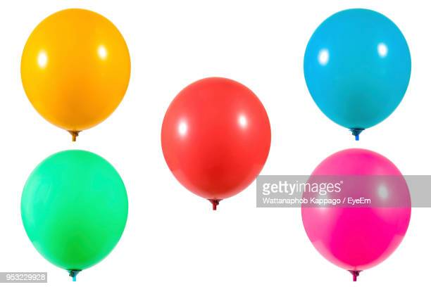 close-up of colorful helium balloons against white background - balloon stock pictures, royalty-free photos & images
