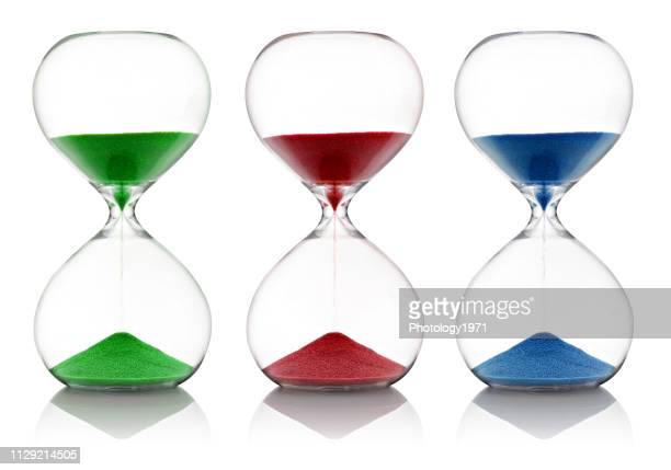 close-up of colorful hourglasses against white background - ampulheta imagens e fotografias de stock