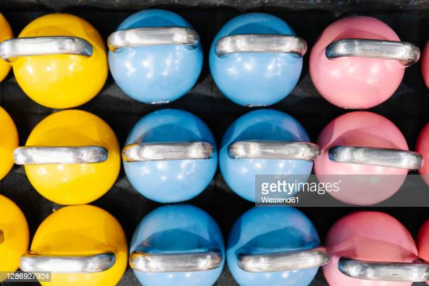 close-up of colorful kettlebells on table in gym - in a row stock pictures, royalty-free photos & images