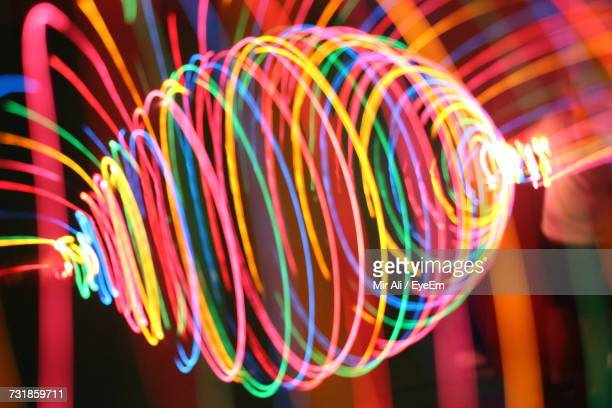 Close-Up Of Colorful Light Painting Against Glow Sticks