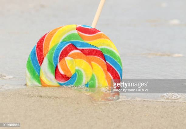 Close-up of colorful lollipop abandoned at the beach