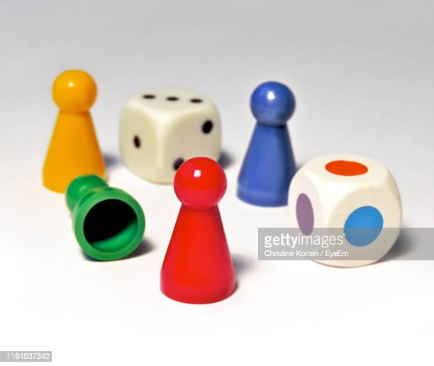 close-up of colorful ludo tokens with dices on white background - board game stock pictures, royalty-free photos & images