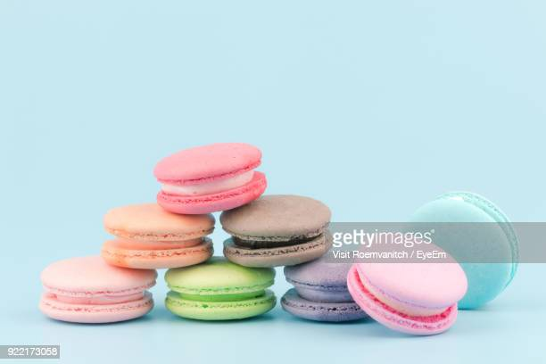 close-up of colorful macaroons against blue background - macarons stock photos and pictures