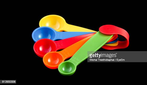 close-up of colorful measuring spoons against black background - measuring spoon stock pictures, royalty-free photos & images