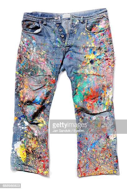 Close-Up Of Colorful Paint On Jeans Against White Background