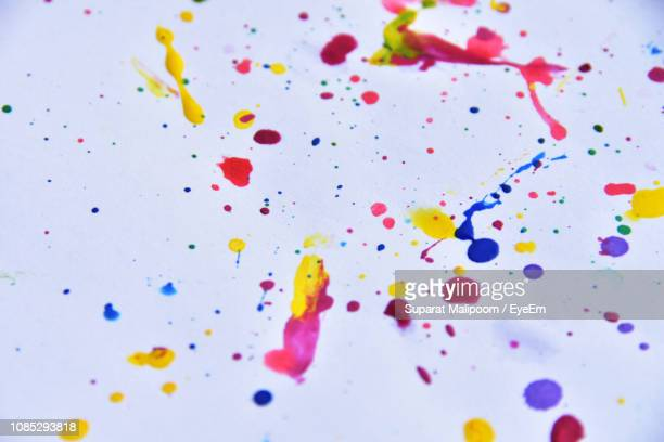 Close-Up Of Colorful Paint Stains On White Paper