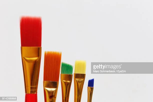 Close-Up Of Colorful Paintbrushes Against White Background