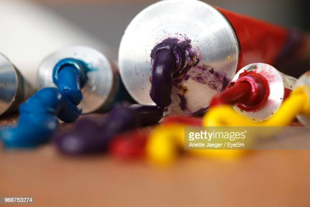 Close-Up Of Colorful Paints With Tubes On Table At Workshop