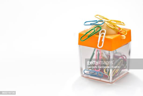 Close-Up Of Colorful Paper Clips With Magnet Container Over White Background