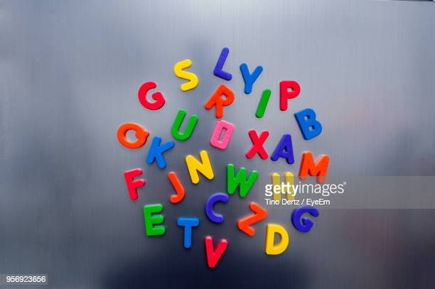 Close-Up Of Colorful Plastic Alphabets On Glass Wall