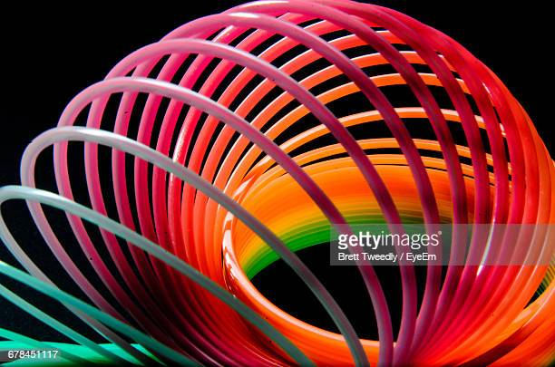 close-up of colorful slinky on black background - metal coil toy stock photos and pictures