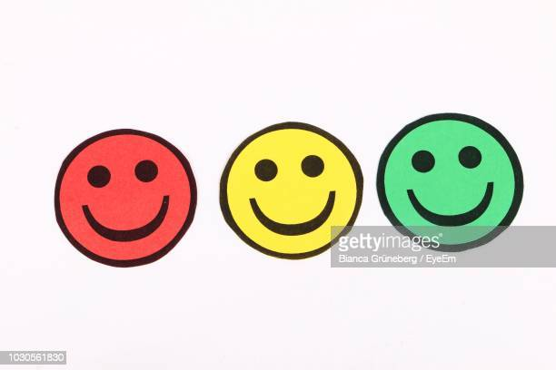 close-up of colorful smiley faces on white background - smiley face stock pictures, royalty-free photos & images