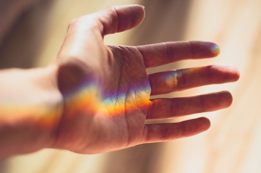 Close-Up Of Colorful Sunlight Falling On Cropped Hand - gettyimageskorea