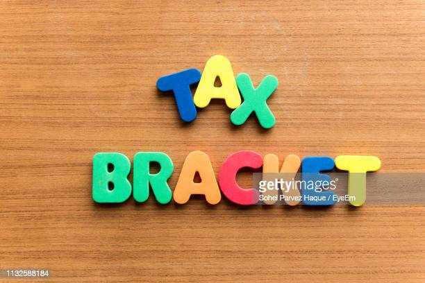 close-up of colorful text on table - tax_bracket stock pictures, royalty-free photos & images