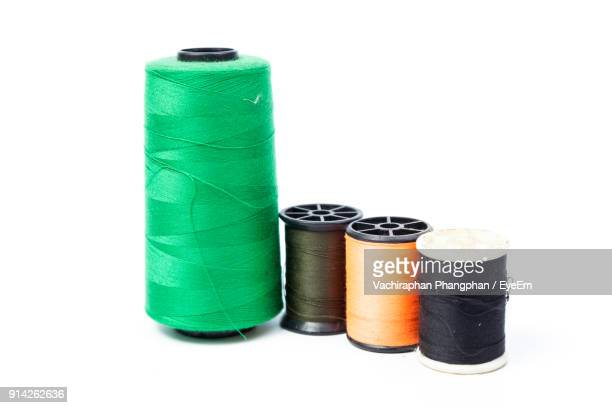 Close-Up Of Colorful Thread Spools Against White Background