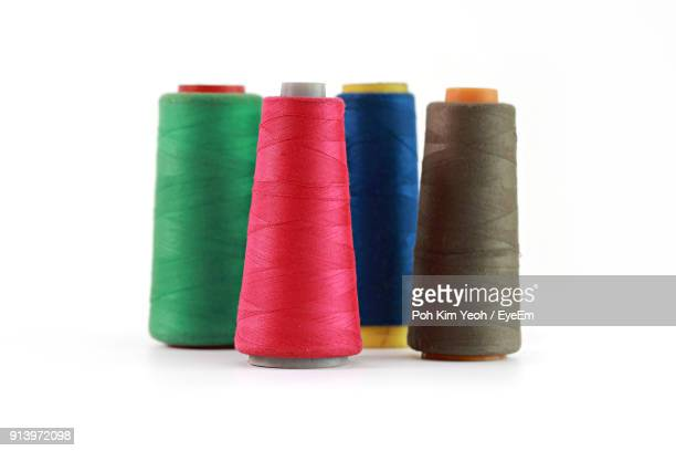 close-up of colorful thread spools over white background - thread stock pictures, royalty-free photos & images