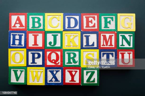 close-up of colorful toy blocks on black background - alphabet stock pictures, royalty-free photos & images