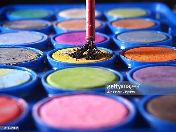 Close-Up Of Colorful Watercolor Paints And Paintbrush
