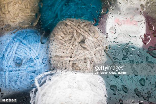 Close-Up Of Colorful Yarn Balls Seen Through Wet Glass Window