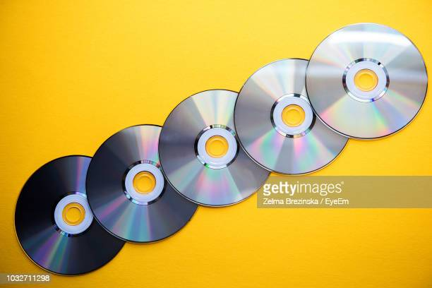 close-up of compact discs over yellow background - compact disc stock pictures, royalty-free photos & images