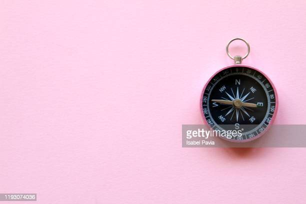 close-up of compass against pink background - east stock pictures, royalty-free photos & images