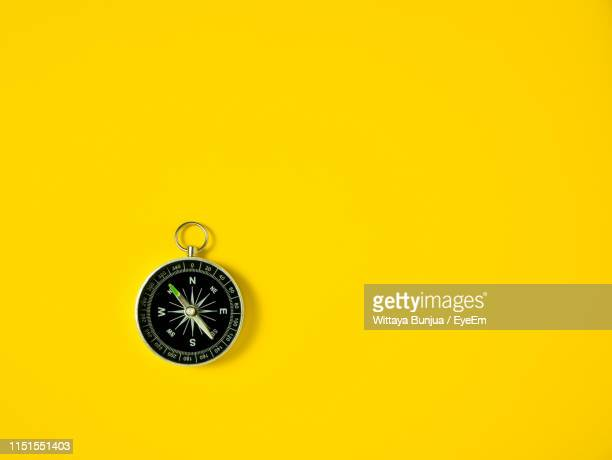close-up of compass against yellow background - compass stock pictures, royalty-free photos & images
