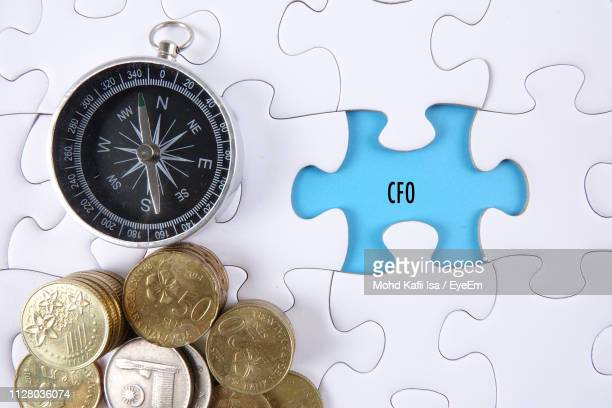 Close-Up Of Compass And Coins On Jigsaw Puzzle With Text