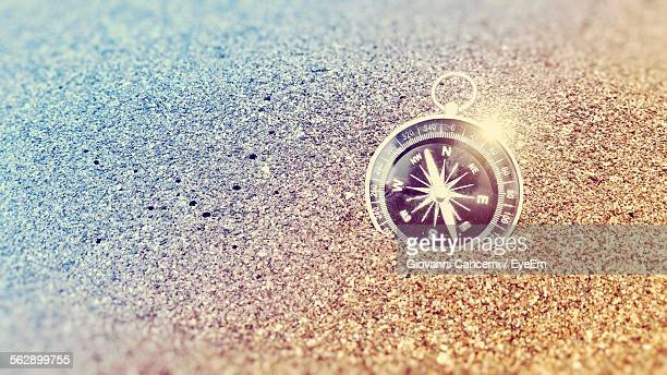 Close-Up Of Compass On Sand In Beach