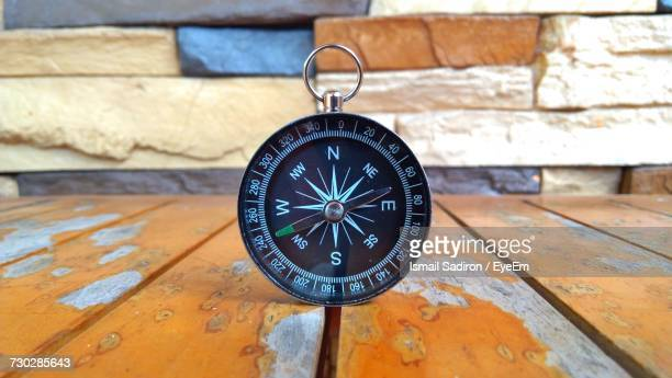 close-up of compass on wooden table against wall - compass stock-fotos und bilder