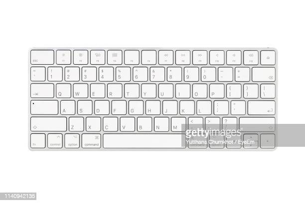 close-up of computer keyboard over white background - computertoetsenbord stockfoto's en -beelden