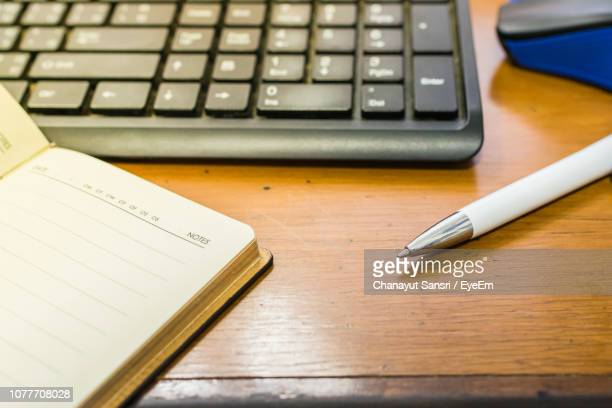 close-up of computer keyboard with pen and book on table - chanayut stock photos and pictures