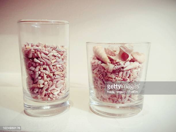 Close-Up Of Conch Shells In Glasses On Table