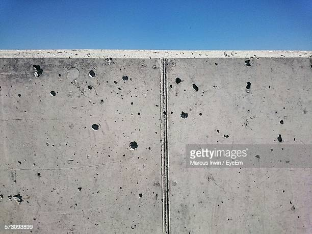 Close-Up Of Concrete Wall Against Clear Blue Sky
