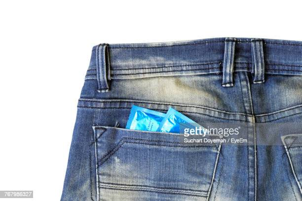 close-up of condoms in jeans pocket over white background - trousers stock pictures, royalty-free photos & images