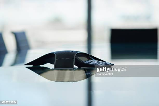 close-up of conference call phone on glass meeting table