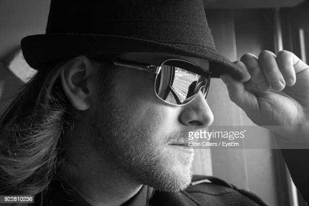 Close-Up Of Confident Man Wearing Sunglasses And Hat