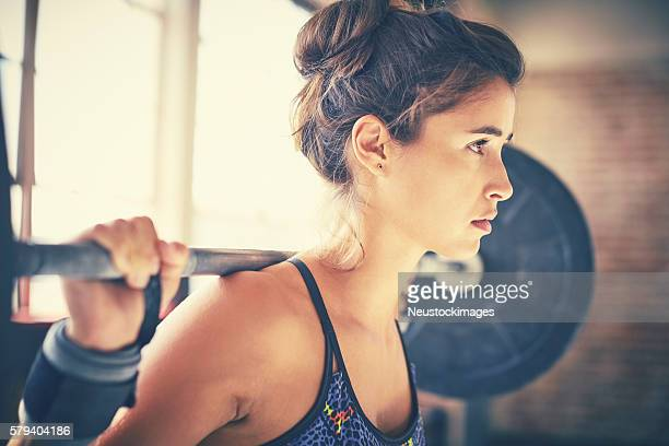 Close-up of confident young female exercising with barbell in gy