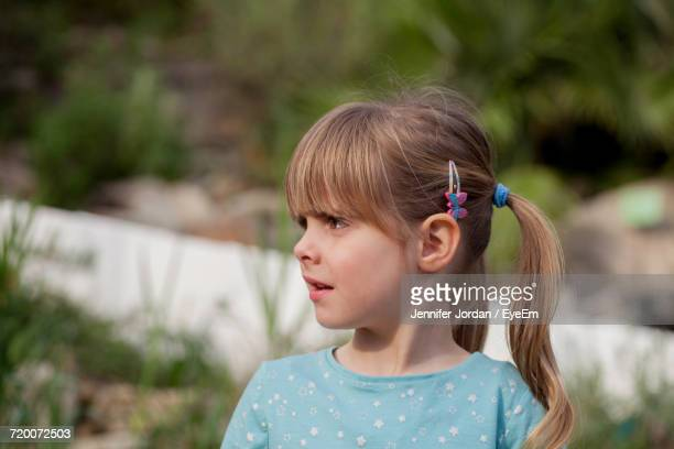 Close-Up Of Confused Girl Looking Away While Standing In Yard