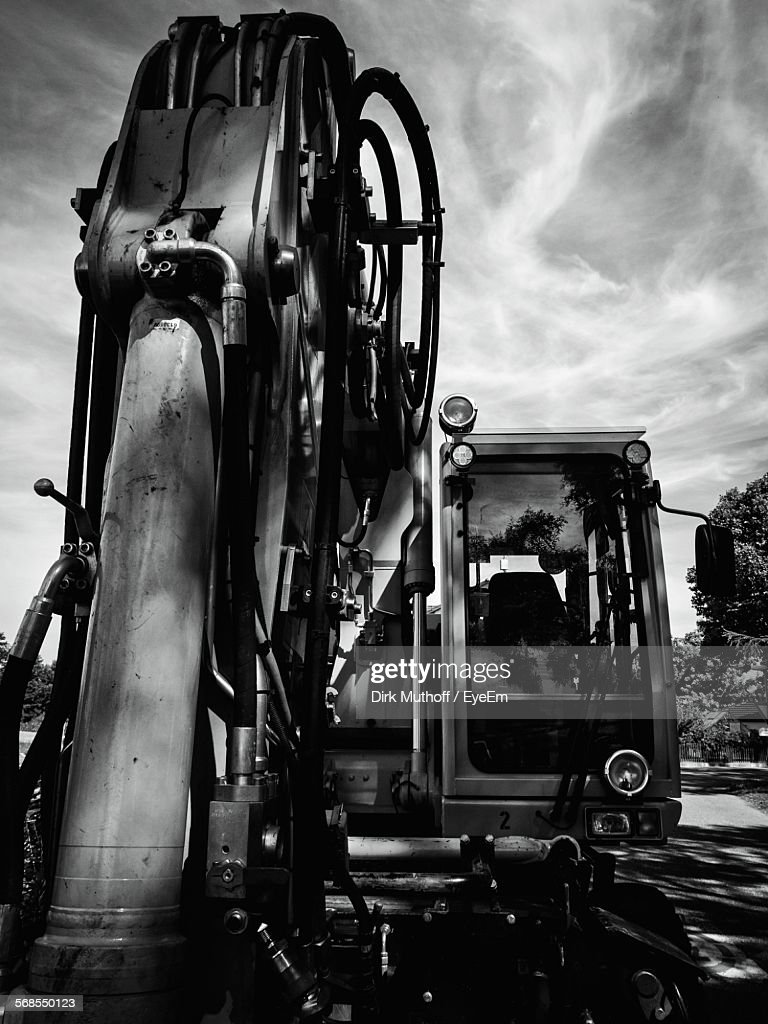 Close-Up Of Construction Machinery On Road Against Cloudy Sky : Stock Photo