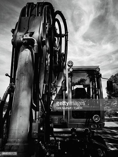Close-Up Of Construction Machinery On Road Against Cloudy Sky