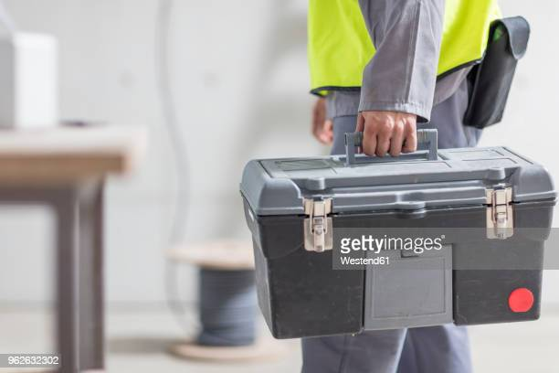 close-up of construction worker carrying tool box - toolbox stock photos and pictures