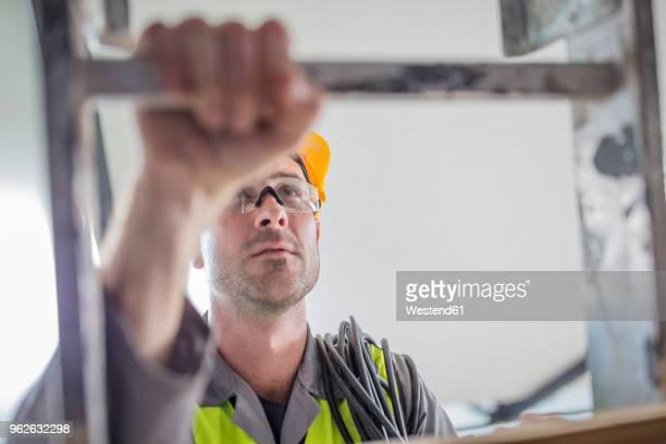 Close-up of construction worker climbing ladder