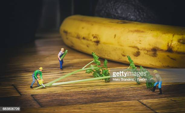 Close-Up Of Construction Worker Figurines Cutting Cilantro By Banana On Wooden Table