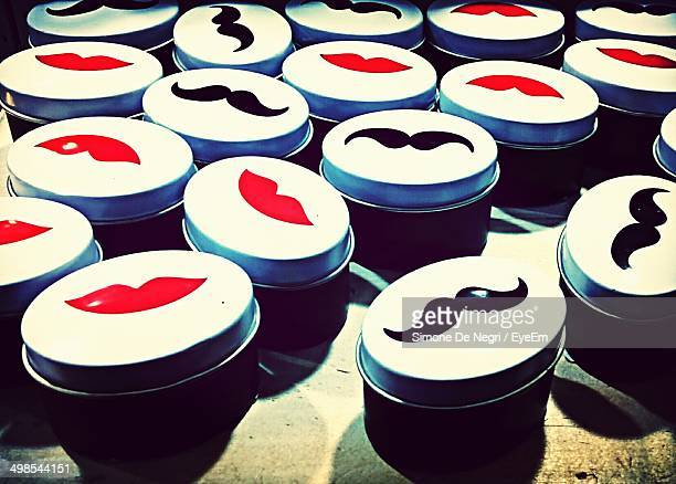 Close-up of containers with moustache representations
